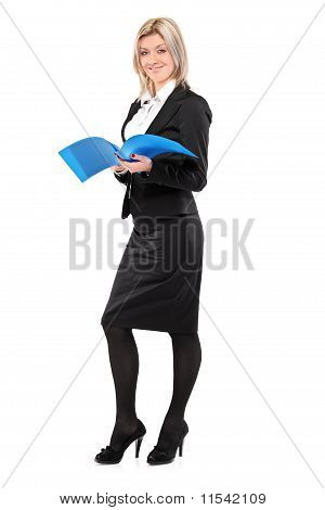 Full Length Portrait Of A Smiling Businesswoman Holding A Document
