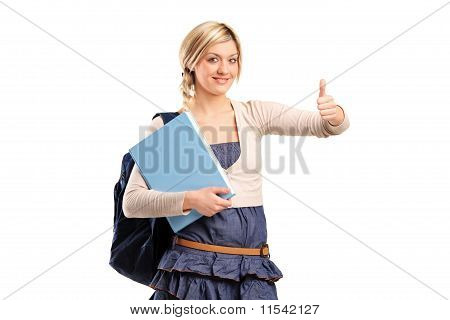 Female Student With A School Bag Holding A Book And Giving Thumb Up