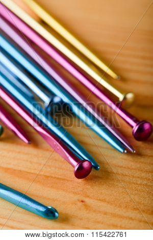 Colorful Set Of Knitting Needles On Wooden Board