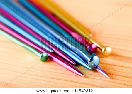 Several Knitting Needles On Wooden Board