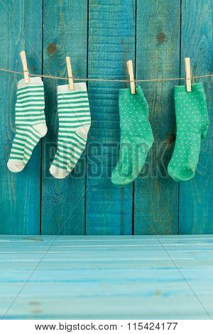 Baby Knitted Woolen Socks On Primako On Turquoise Wooden Background