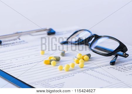 Pills and glasses on top of hospital form.