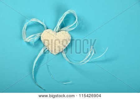 Gypsum Heart With Flowers And Ribbon On Blue Background
