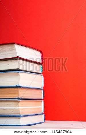 Open hardback book on wooden deck table and red background
