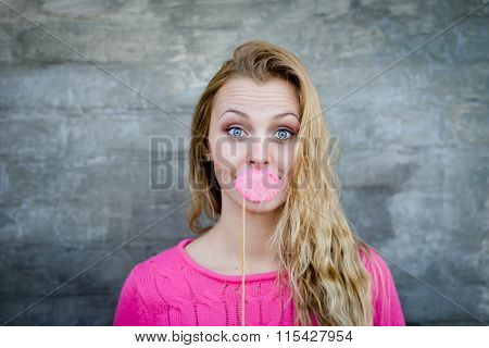 Pretty woman with long blond hair holding moustache on stick
