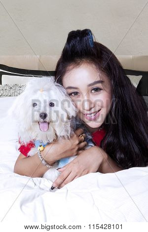 Cheerful Girl And Maltese Dog In The Bedroom