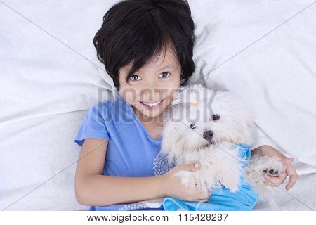 Closeup Of Girl And Dog On Bed