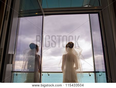The attractive bride is standing on the balcony.