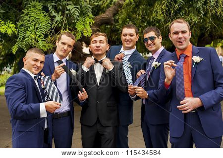 Friends of the groom are showing their ties.
