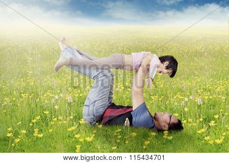 Happy Father And Daughter Playing On Meadow