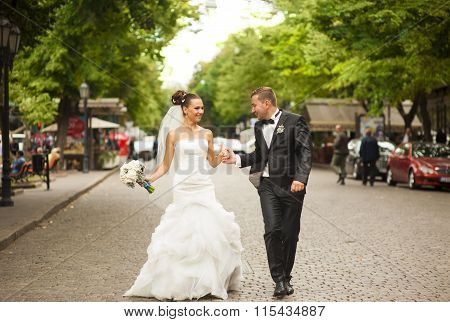 The newlyweds are walking on the street.