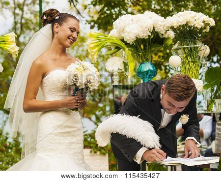 The groom is signing his signature.