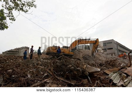 Building Demolition Site With Excavator And Workers