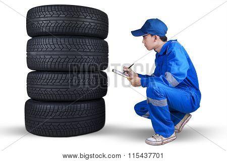 Male Mechanic Checks A Pile Of Tires