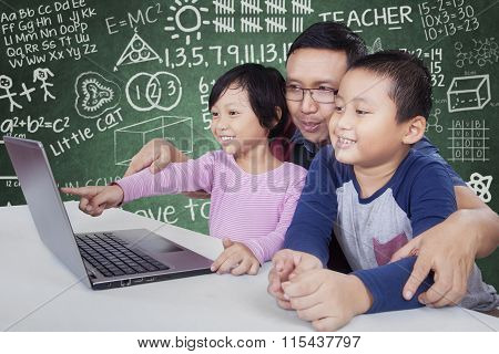 Male Teacher And His Students Using Laptop