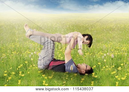 Man And Daughter Playing On Blossom Meadow