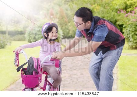 Man Teach His Daughter To Ride Bicycle