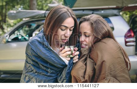 Women inside of sleeping bags holding coffee cup