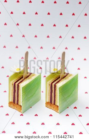 Colorful cake on hearts background