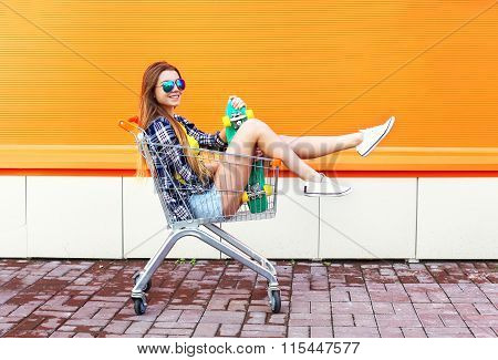Fashion Smiling Cool Girl Having Fun Sitting In Shopping Trolley Cart With Skateboard