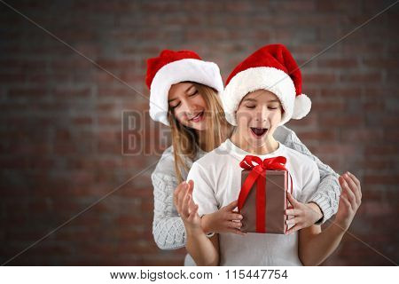 Happy sister and brother with gift box on brick wall background