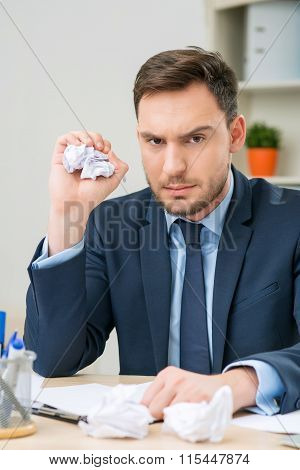 Nice worker playing with paper at the table