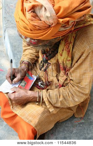 A Holy Sadhu Writing On A Paper