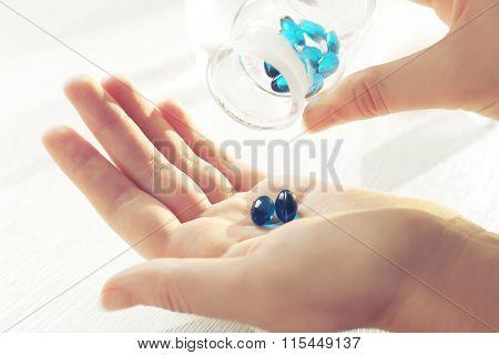 Transparent blue pills in female hands