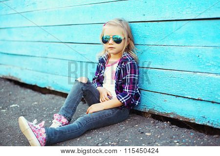 Fashion Cool Child Wearing A Sunglasses And Checkered Shirt Sitting In City