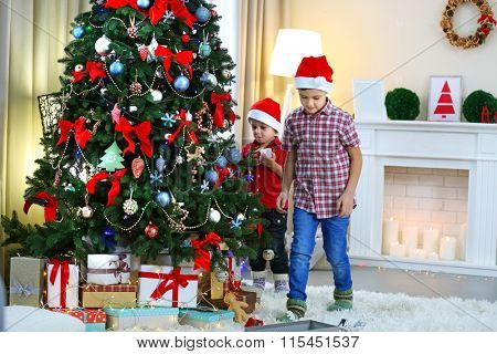 Two cute small brothers decorating Christmas tree