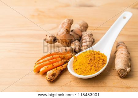 Fresh And Grounded Turmeric Roots On Wooden Surface