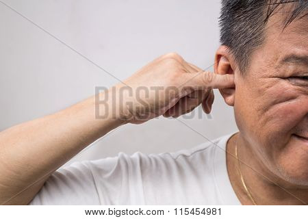 Man Un-hygienically Cleaning Ear Using Finger With Ticklish Expression