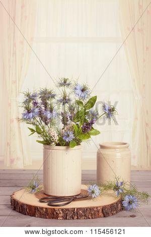 Wild flower arrangement with scissors against a brightly lit window