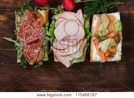 baguette sandwich with salmon and ham,  lettuce and arugula