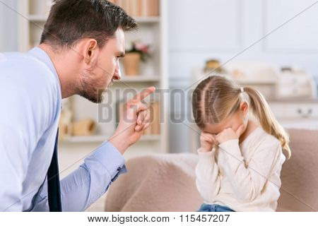 Strict father punishing his daughter