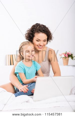 Mom and daughter are in front of laptop.