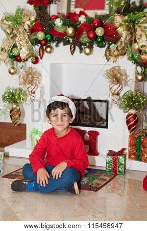 Boy Sitting In Front Of Fireplace