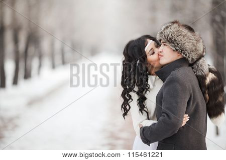 Exotic asian bride and groom kissing in middle of snowy winter alley. Young man wearing coat, fur ha