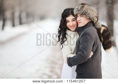 Beautiful wedding couple, exotic asian bride and groom embraced. Young man in winter coat, fur hat,