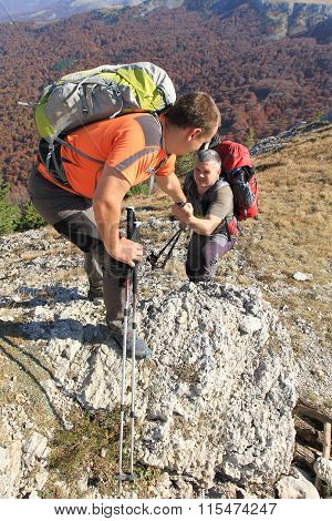 Tourist man helps someone to climb the mountain.