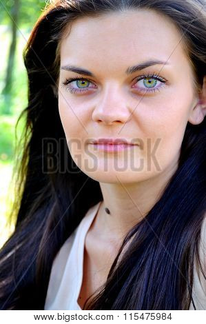 Young and beautiful brunette woman with bright green eyes