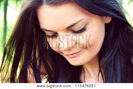Young and beautiful brunette woman looking away with a shy smile
