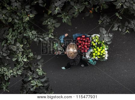 Top view of the fruit seller walking with bicycle along the street. Vietnam
