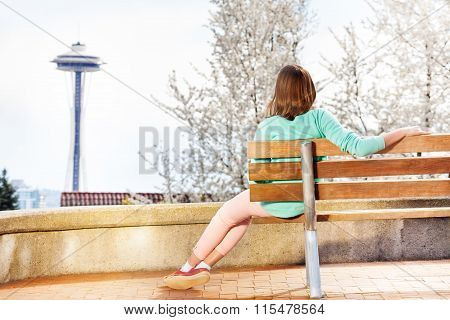 Young woman on bench look at space needle