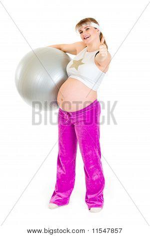 Lächelnd schwangere Frau Fitness-Ball halten und mit Daumen hoch Geste
