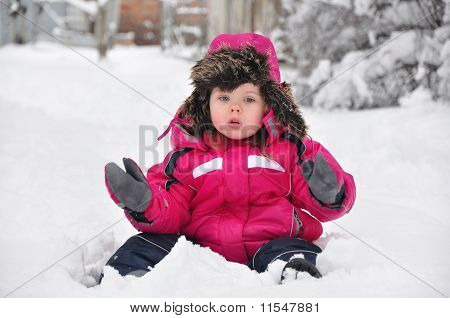 Cute toddler girl sitting on snow