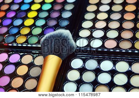 Set of different eyeshadows with cosmetic brush