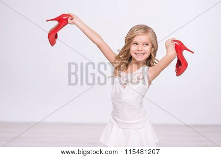 Cheerful little girl holding red shoes