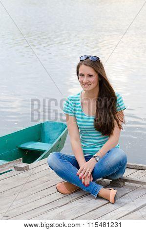 Beautiful sexy female wearing sailor striped dress sitting near boat