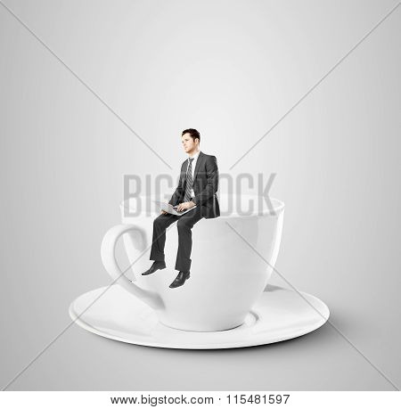 Businessman Sitting On Coffee Cup